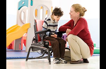 A caregiver has activated the dynamic spring feature on a Standard base Rifton Activity Chair so a child with autism can rock to calm himself