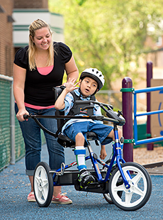 A therapist and young boy using the Rifton adaptive tricycle to build motor skills