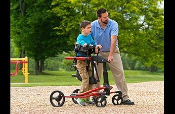 A young boy with his caretaker in a Rifton Pacer gait trainer using the utility base on wood chips.