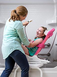 A caretaker bathes a young girl in a Rifton Wave bath chair.