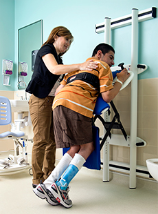 A young man using a Rifton Support Station with a caregiver assisting.
